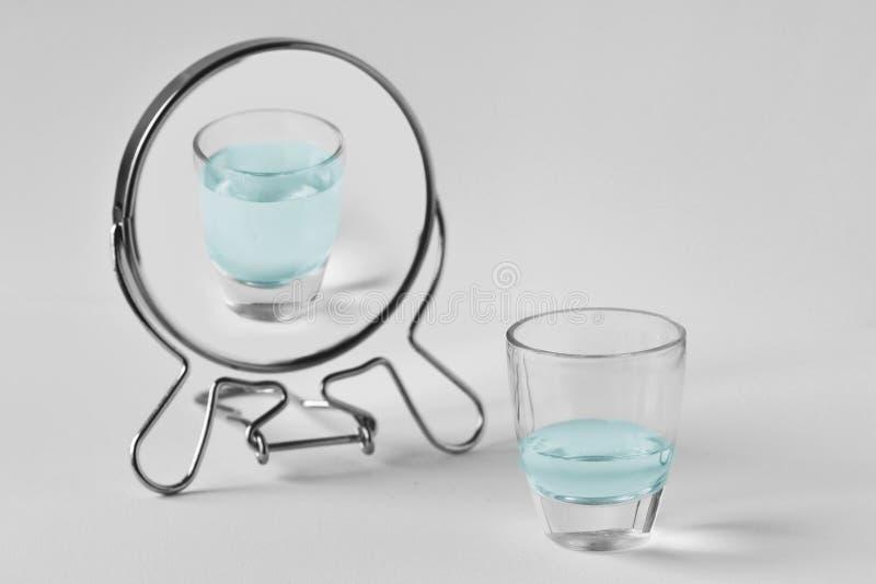 Vidro de água meio vazio que olha no espelho e que vê-se como um vidro completo - conceito do otimismo imagem de stock