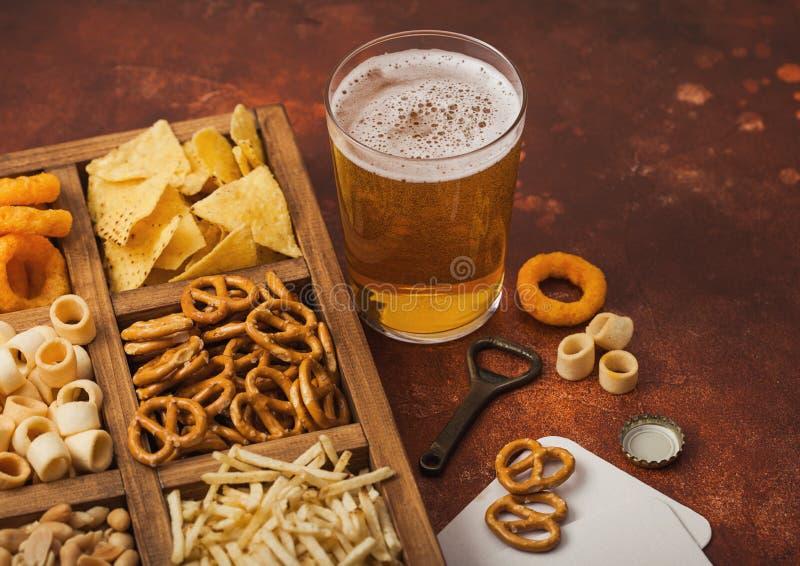 Vidro de cerveja e de abridor de cerveja de alcatrão com caixa de salgadinhos sobre fundo castanho Pretzel, bastões de batata sal fotos de stock