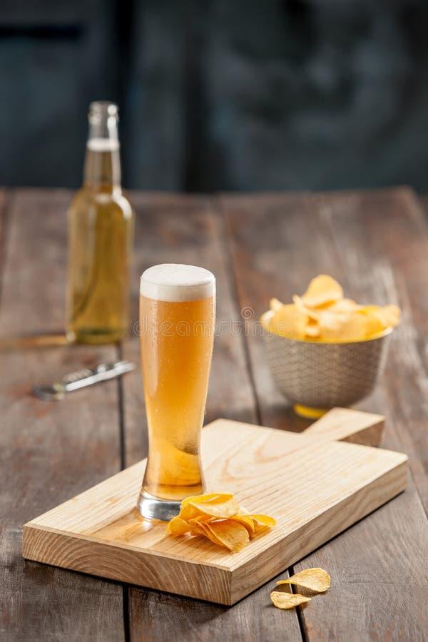 Vidro de cerveja e microplaquetas de batata, pistaches isolados em um branco fotografia de stock royalty free