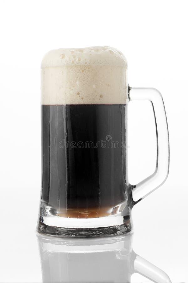 Vidro de cerveja preto no fundo branco imagem de stock