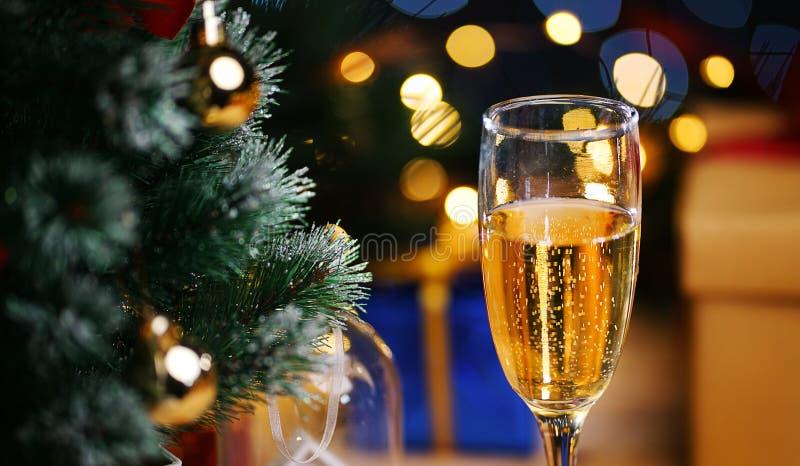 Vidro de Champagne Beside Christmas Tree Feche acima do tiro imagem de stock royalty free