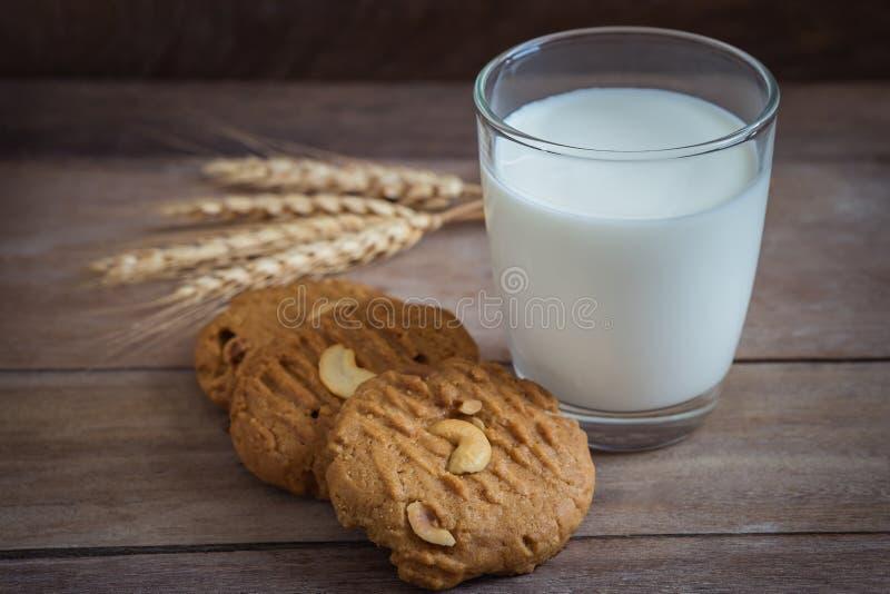 Vidro de cookies do leite e do amendoim no fundo de madeira fotografia de stock royalty free