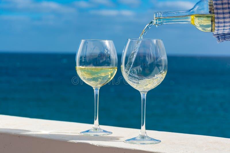 Vidro de derramamento do garçom do vinho branco no terraço exterior com mar v imagens de stock royalty free