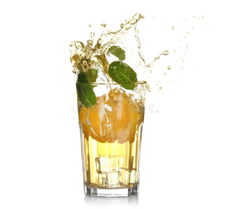 Vidro de espirrar a limonada com os citrinos no fundo branco imagens de stock