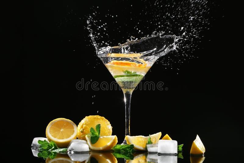 Vidro de espirrar o cocktail e as fatias de citrinas no fundo preto foto de stock royalty free