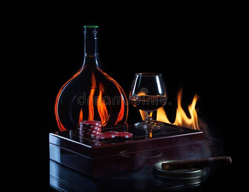 Vidro de garrafa do conhaque com marcadores e charuto do pôquer foto de stock
