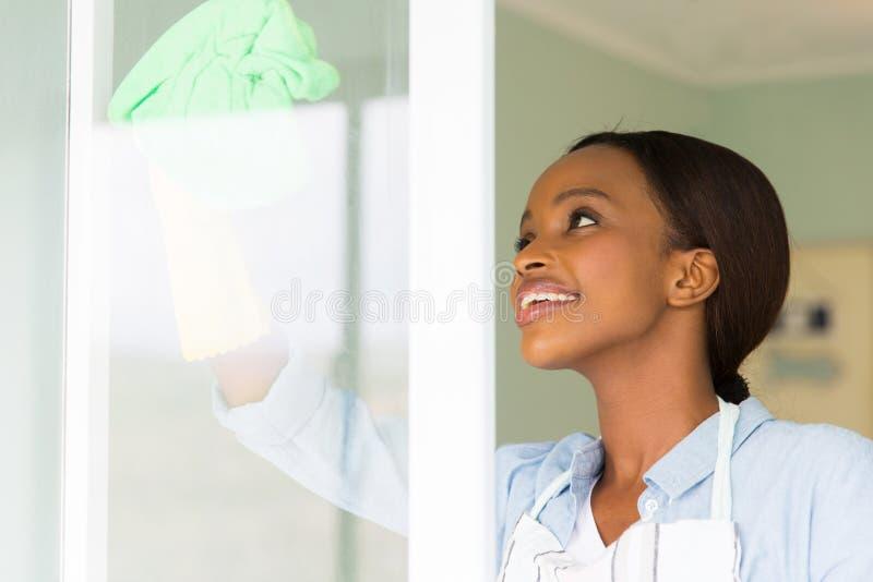 Vidro de janela da limpeza da mulher imagem de stock