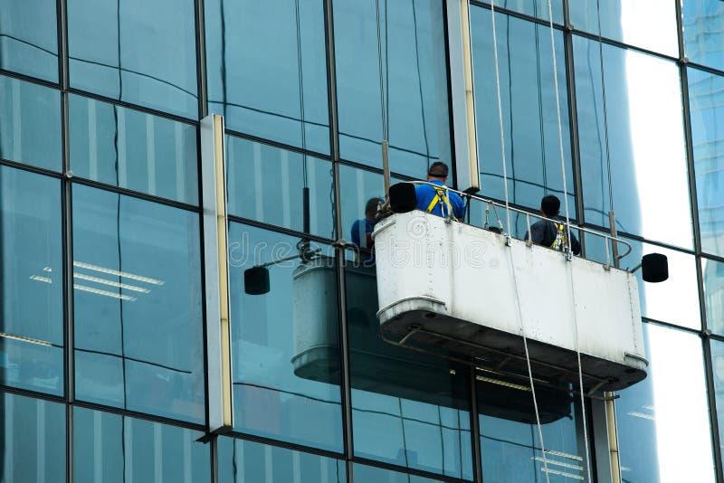 Vidro de janelas limpo do berço do guindaste dos trabalhadores da elevação imagens de stock
