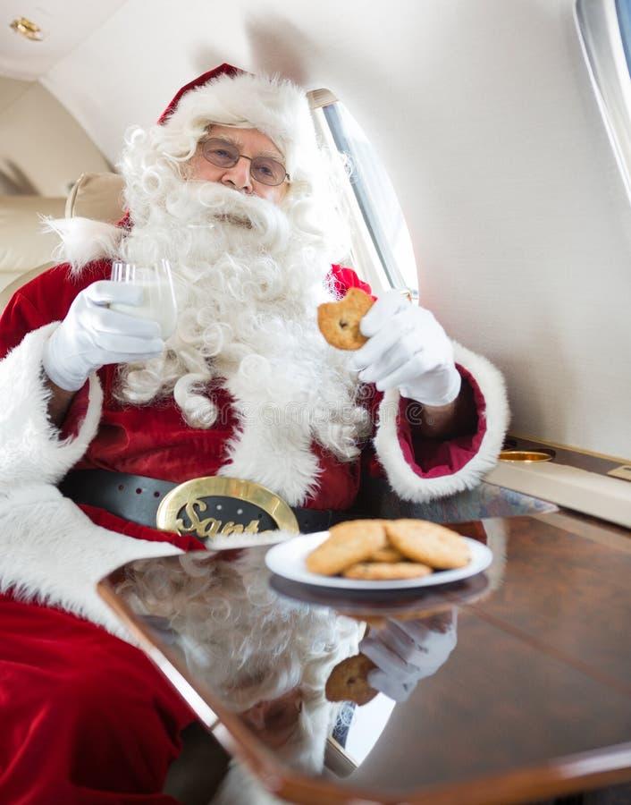 Vidro de leite de Santa Eating Cookies While Holding dentro imagens de stock
