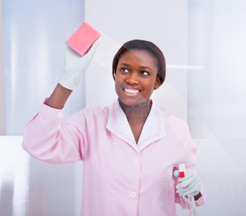 Vidro de limpeza da empregada fêmea no hotel imagem de stock royalty free