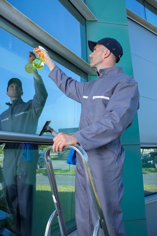 Vidro de limpeza do trabalhador masculino maduro feliz imagem de stock