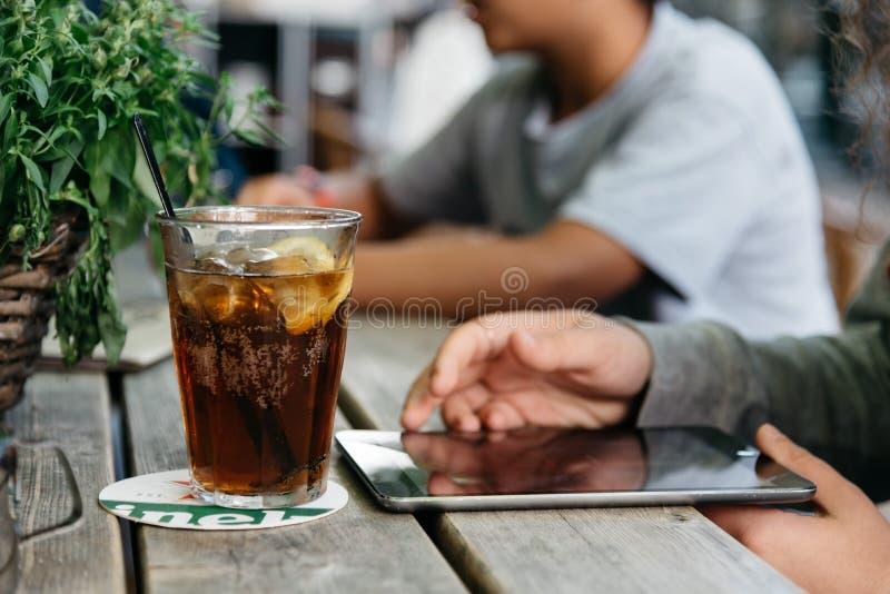 Vidro de refrescamento da cola na tabela de madeira em uma barra quando o jovem for fotos de stock royalty free