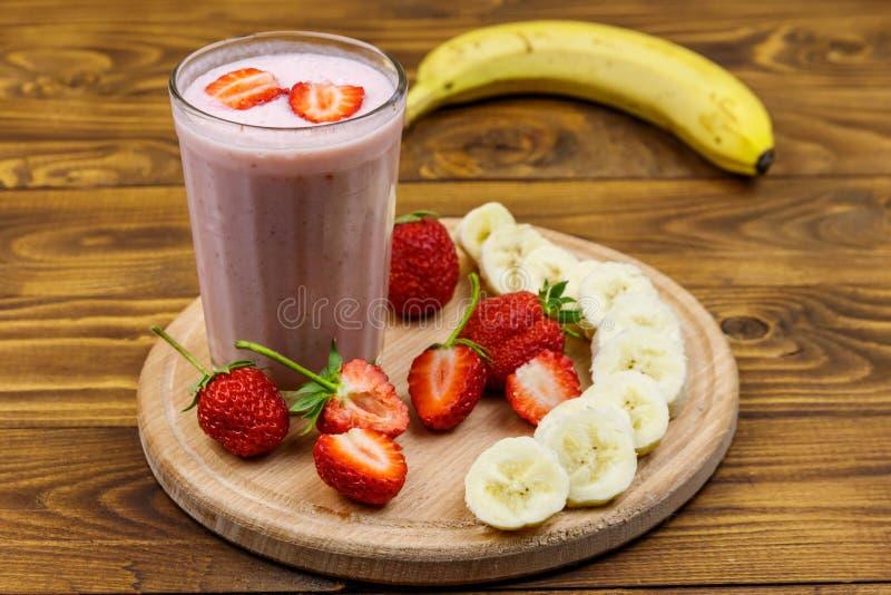 Vidro de suco fresco de morango e banana sobre mesa de madeira fotografia de stock royalty free