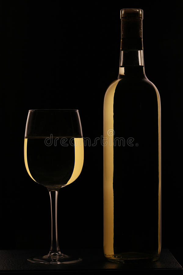 Vidro de vinho cheio do vinho branco com frasco fotos de stock royalty free