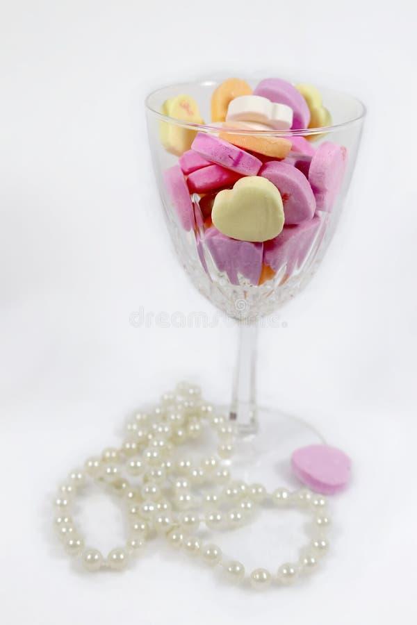Vidro de vinho de vidro cortado enchido com os corações pasteis dos doces com corda das pérolas que encontram-se no fundo fotografia de stock royalty free