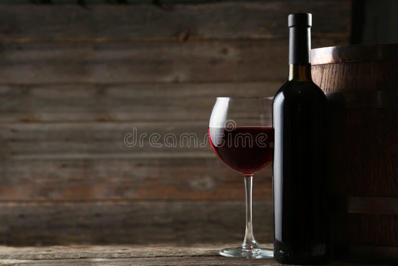 Vidro de vinho tinto com garrafa e tambor no fundo de madeira foto de stock