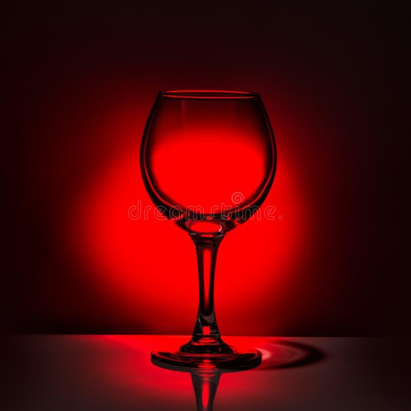 Vidro de vinho vazio da silhueta bonita no backgroun vermelho e preto fotografia de stock