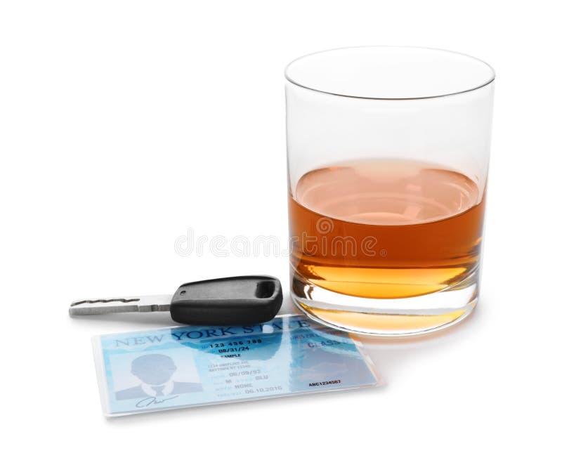 Vidro do álcool, da chave do carro e da carteira de habilitação no branco Conceito de condução responsável imagem de stock royalty free