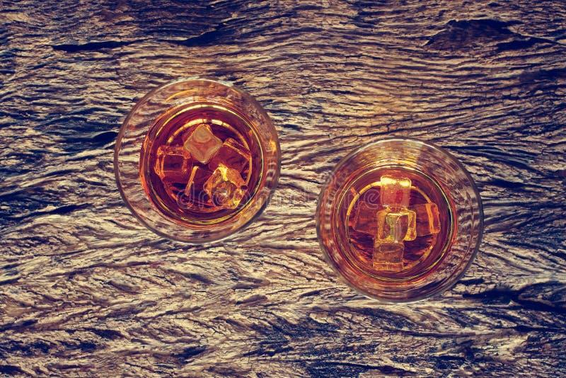 Vidro do bourbon do uísque com gelo na textura de madeira foto de stock