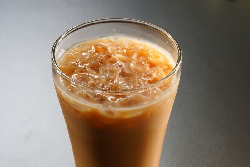 Vidro do café leitoso com gelo em Ásia no fundo cinzento fotos de stock