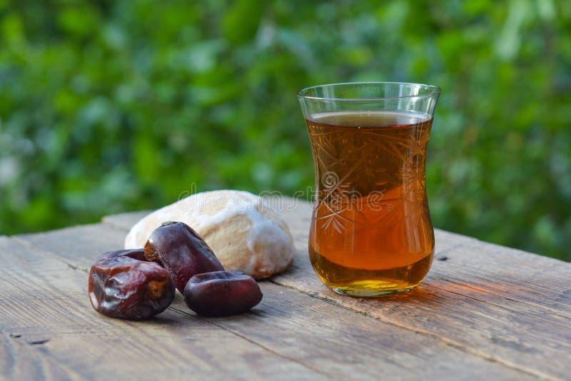 Vidro do chá perfumado com datas e pão-de-espécie foto de stock