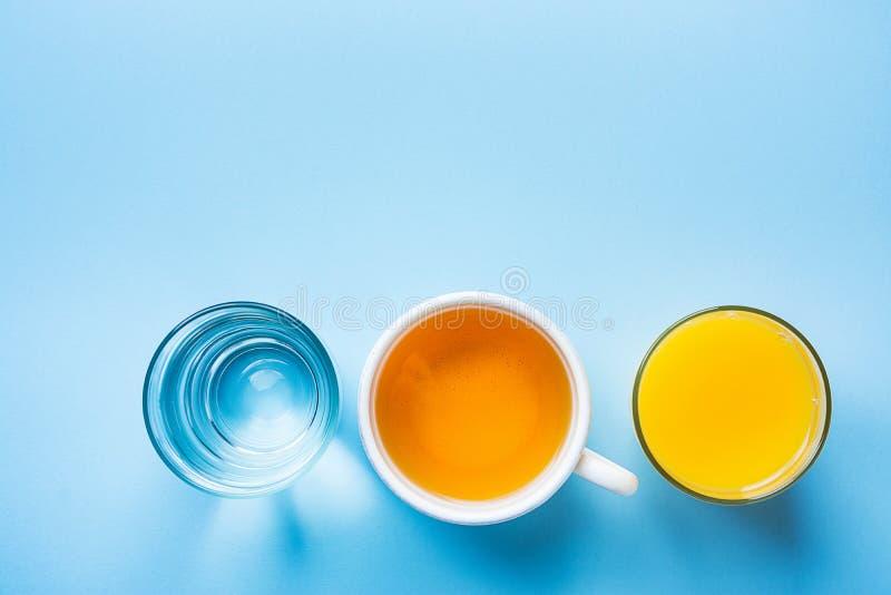 Vidro do citrino alaranjado recentemente pressionado Juice Herbal Tea Water na luz - fundo azul Bebidas saudáveis do café da manh imagens de stock royalty free