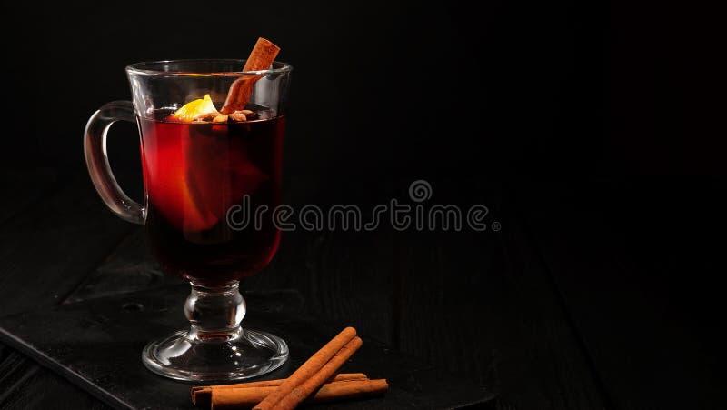 Vidro do close up do vinho ferventado com especiarias com laranja e canela no fundo preto escuro, lugar para o texto imagens de stock
