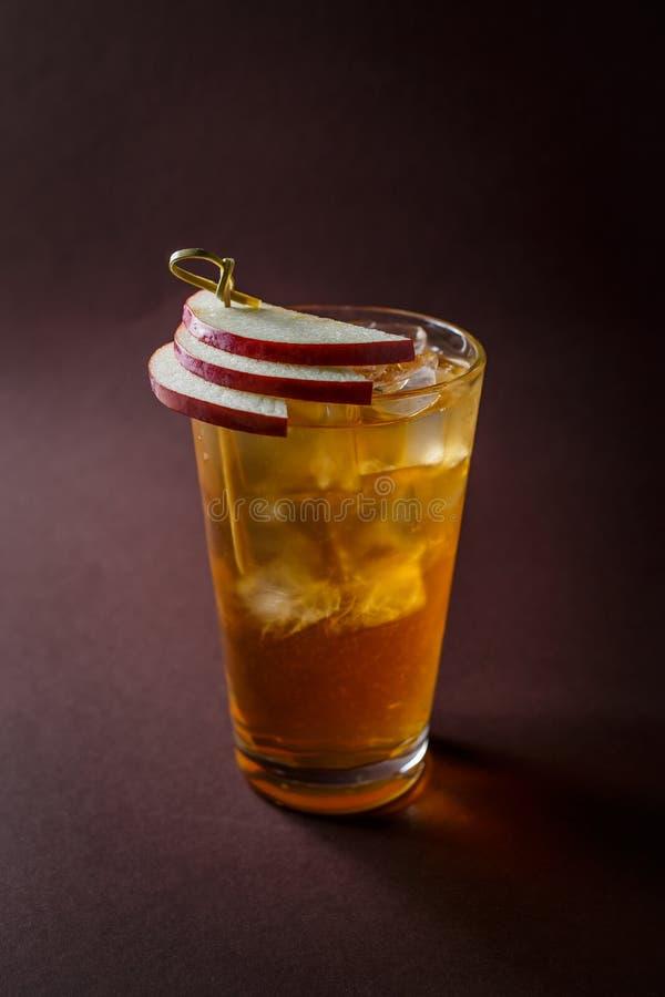 Vidro do cocktail do uísque com fatias de maçã no Br escuro elegante fotos de stock