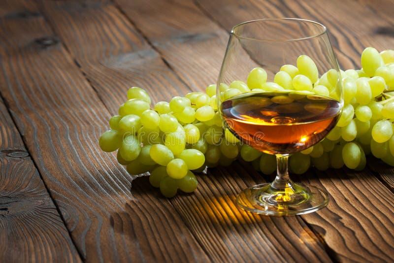 Vidro do conhaque e grupo de uvas fotos de stock royalty free