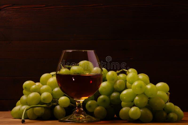 Vidro do conhaque e grupo de uvas fotografia de stock