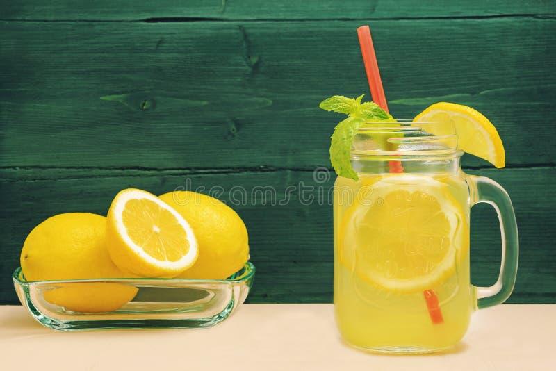 Vidro do frasco de pedreiro da limonada do limão com limões e palha na tabela e no fundo de madeira imagens de stock royalty free