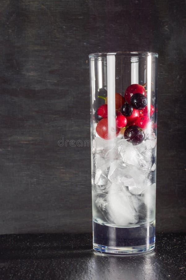 Vidro do gelo com os corintos pretos e água vermelhos das groselhas da baga Cocktail de refrescamento Bebida do verão fotos de stock royalty free