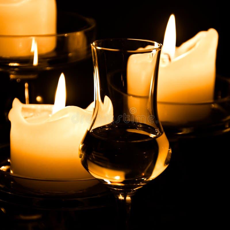 Vidro do Grappa e das velas imagens de stock royalty free