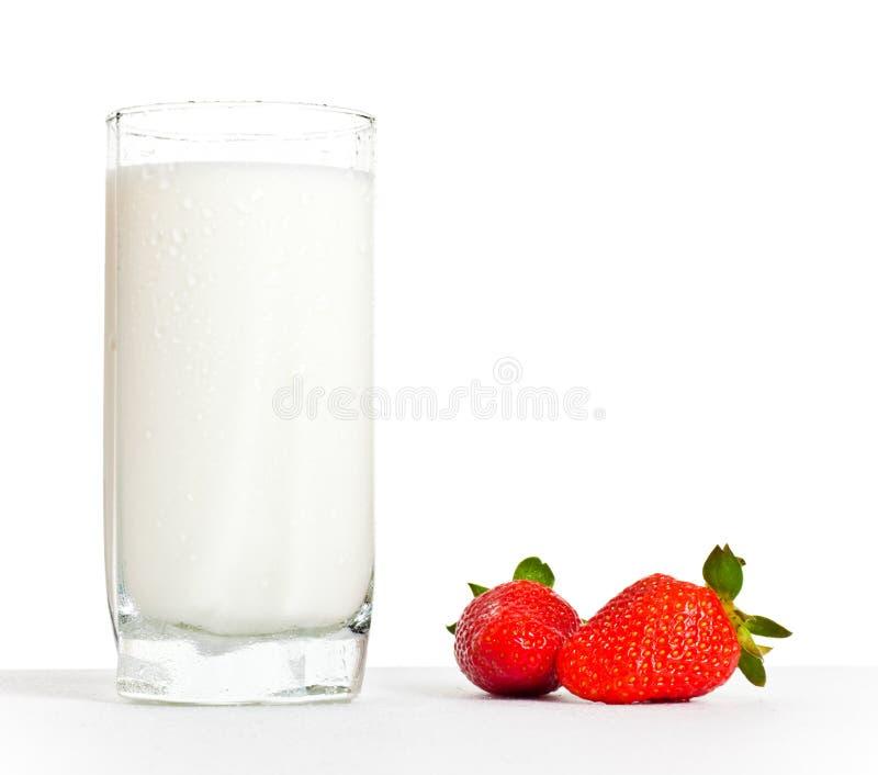 Vidro do leite e das duas morangos imagem de stock royalty free