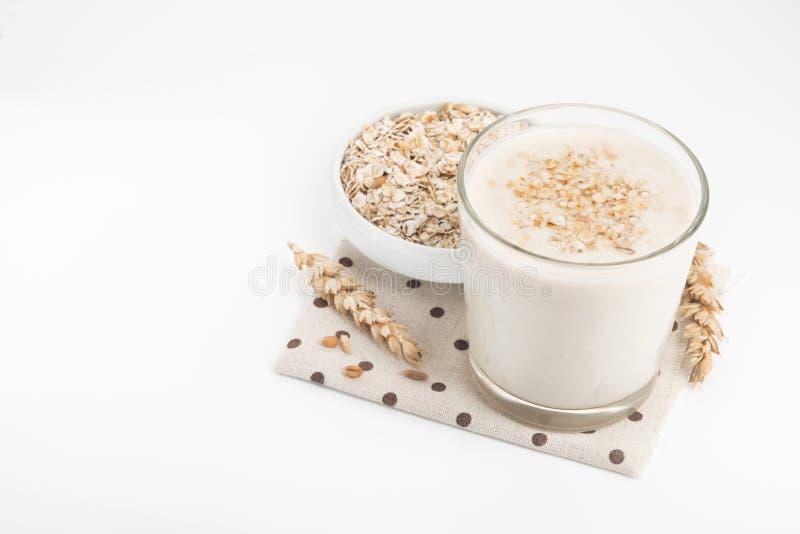 Vidro do leite e das gr?es da aveia na bacia branca imagem de stock