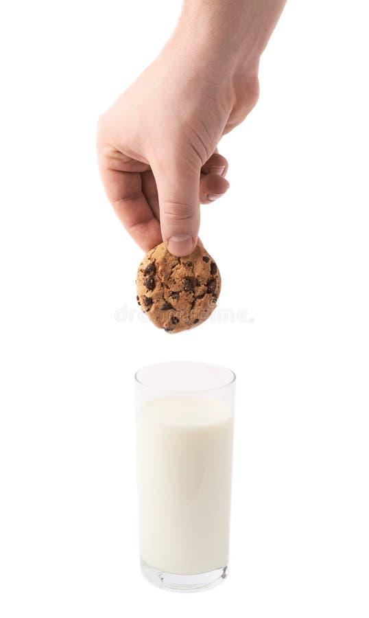 Vidro do leite e de uma mão com a cookie isolada sobre o fundo branco fotos de stock