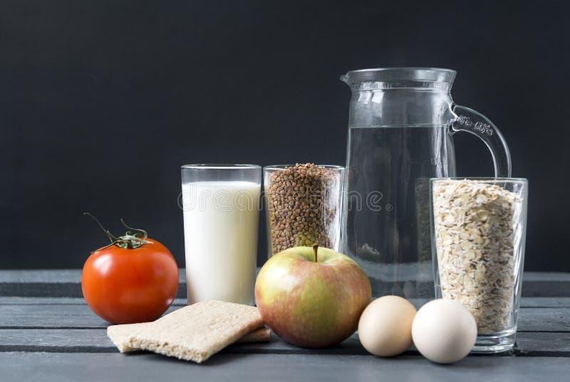 Vidro do leite, trigo mourisco, flocos da aveia nos vidros, jarro de água, tomate, Apple, 2 ovos, pão em um fundo escuro imagens de stock