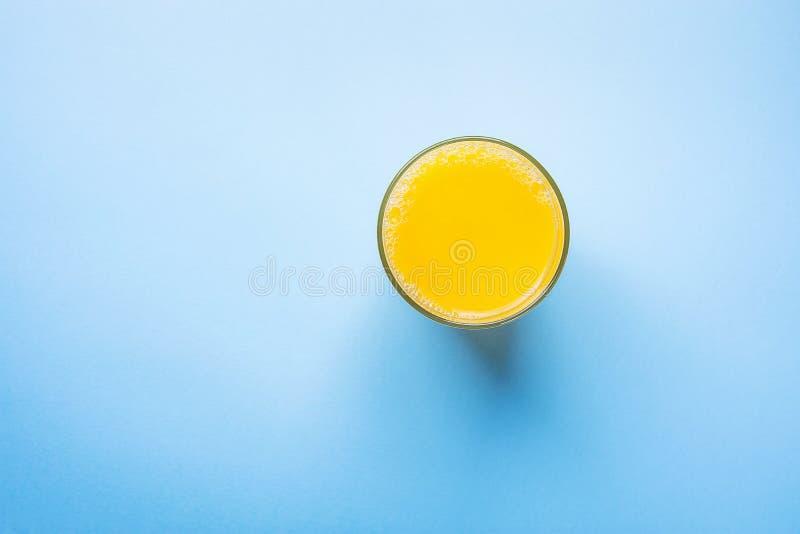 Vidro do suco alaranjado recentemente pressionado do citrino na luz - fundo azul Manhã saudável do café da manhã da desintoxicaçã fotografia de stock royalty free