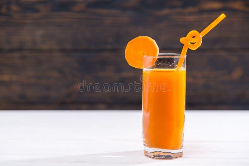 Vidro do suco de cenoura completamente das vitaminas com palha imagem de stock royalty free