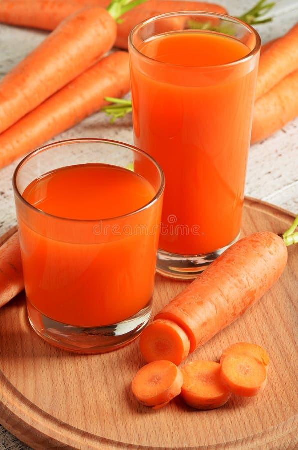 Vidro do suco de cenoura e de cenouras frescas no fundo de madeira branco imagens de stock royalty free