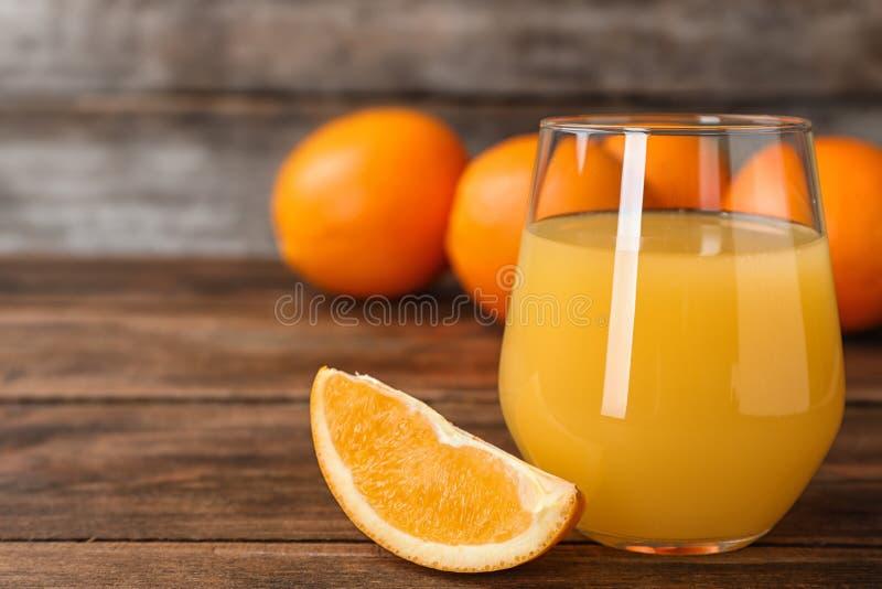 Vidro do suco de laranja e fatia de fruto fresco na tabela Espaço para o texto fotos de stock royalty free