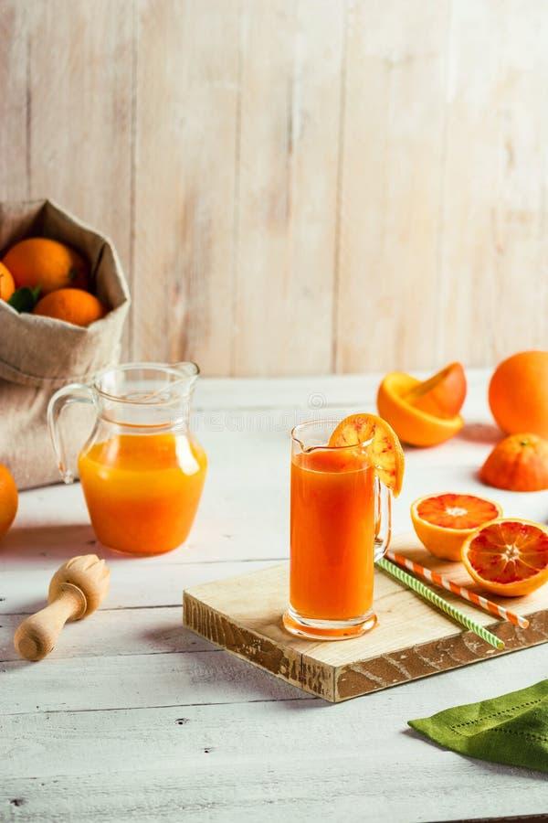 Vidro do suco de laranja e de laranjas pigmentadas pressionados frescos na tabela de madeira Humor brilhante do verão Vista super foto de stock royalty free