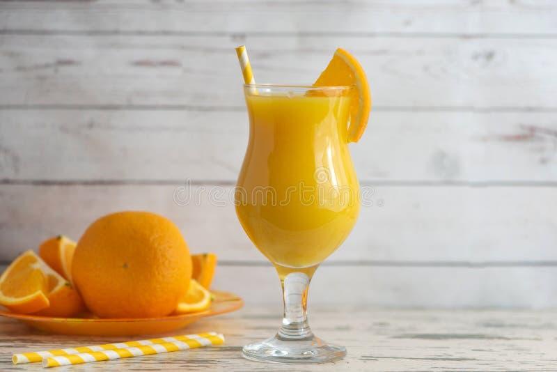 Vidro do suco de laranja fresco no fundo de madeira claro Vista lateral imagem de stock royalty free