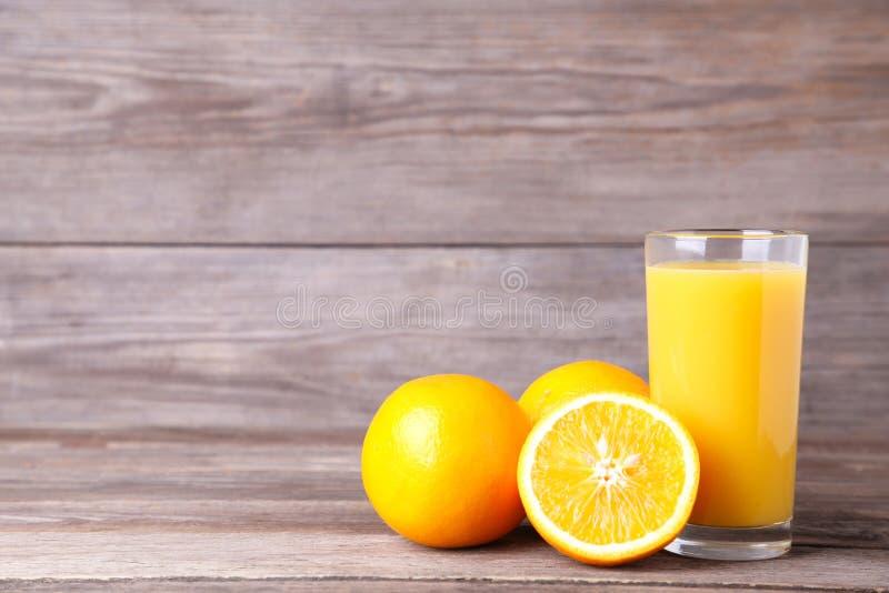 Vidro do suco de laranja no fundo de madeira fotografia de stock royalty free