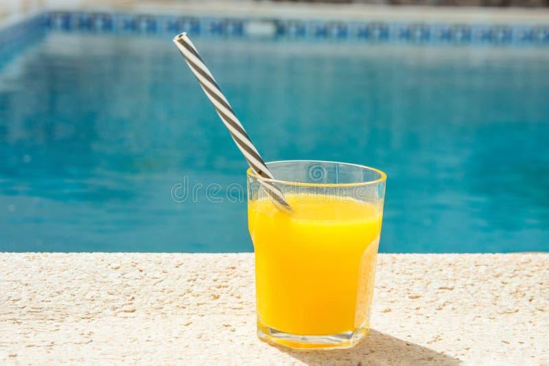 Vidro do suco de laranja recentemente pressionado dos frutos tropicais com a palha listrada que está na plataforma da piscina Luz fotografia de stock royalty free