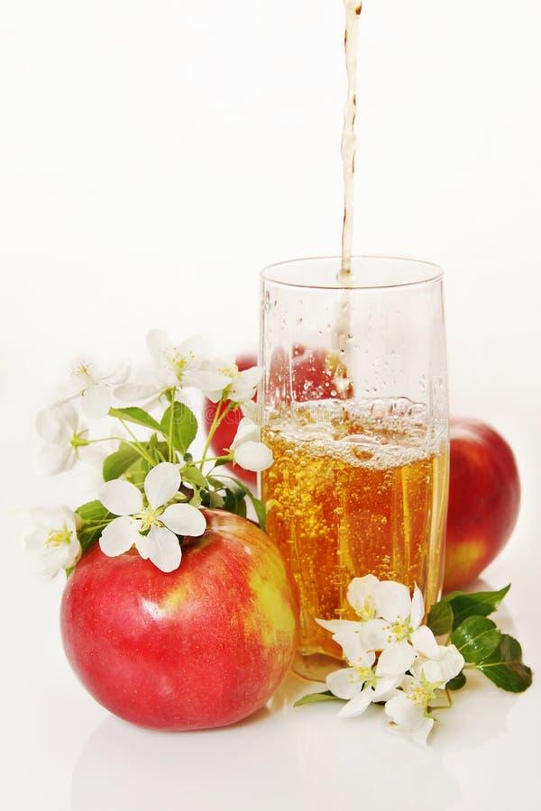 Vidro do suco de maçã fresco com as maçãs e flores vermelhas maduras foto de stock royalty free