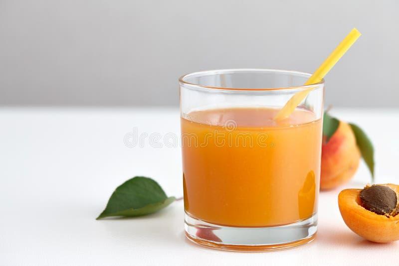Vidro do suco fresco do abricó com palha amarela fotografia de stock