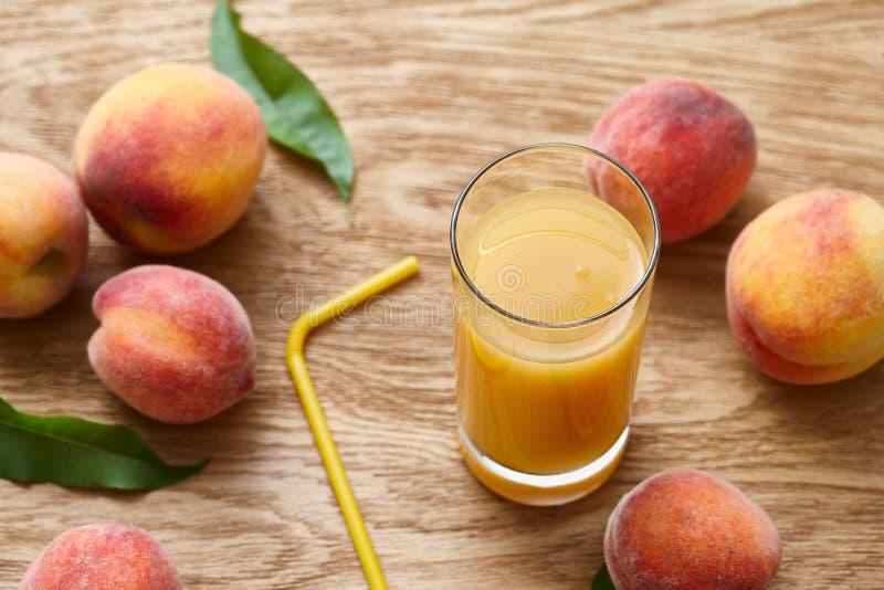 Vidro do suco fresco do pêssego e de frutos maduros imagem de stock royalty free