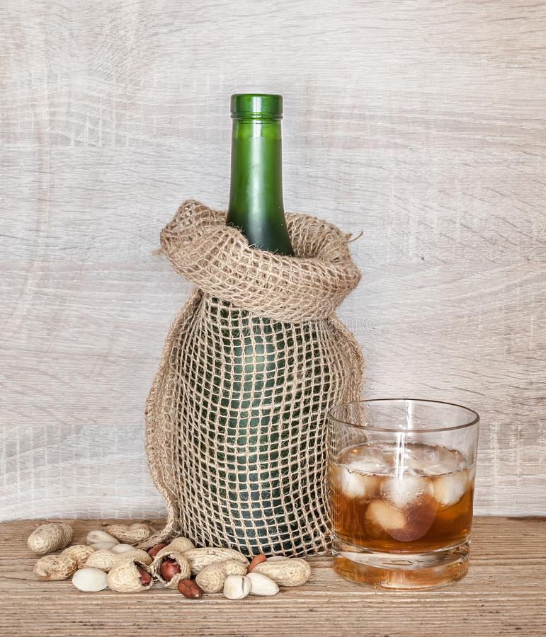 Vidro do uísque com gelo e de uma garrafa envolvida no saco decorativo da lona foto de stock royalty free