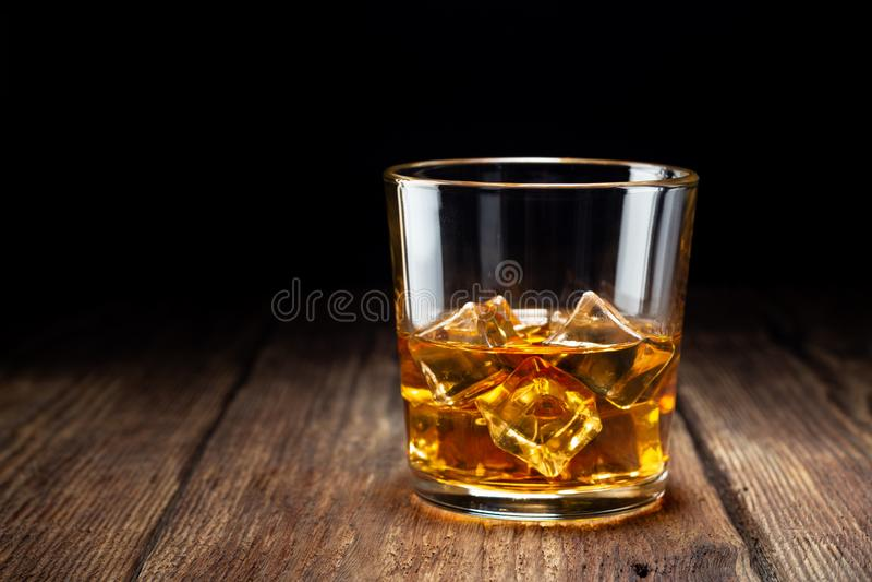 Vidro do uísque com gelo na tabela de madeira imagem de stock royalty free
